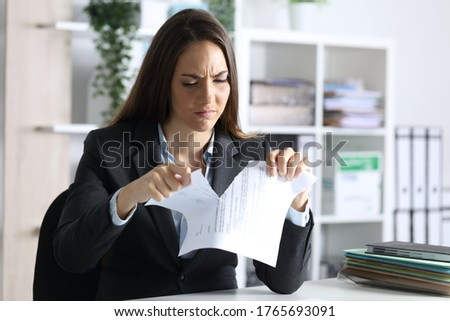Angry executive woman breaking contract document sitting on a desk in the office at night Foto d'archivio ©