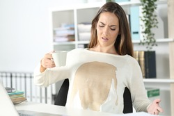 Angry executive woman with spilled coffee over her shirt holding cup sitting on a desk at office