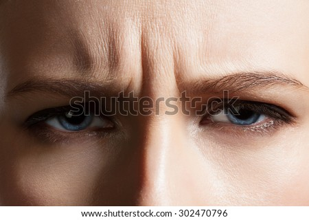 Angry face of a young woman with facial wrinkles closeup #302470796