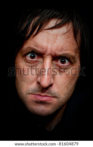 Angry face of caucasian man, close up low key portrait