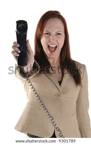 Angry female executive holding the phone receiver at arms length and screaming