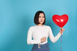 angry, ferocious young Asian woman holds a flying balloon in the shape of a heart and clenches her hand into a fist , isolated on a blue background.