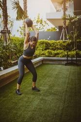 Angry fitness female person does physical exercises holding and throwing fitness ball outside in daytime. Thailand vacation and workout.
