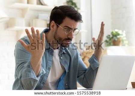 Angry frustrated annoyed young adult man consumer feel rage looking at computer notebook screen furious about laptop pc problem, bad software failure, system virus or malfunction sit at home table Сток-фото ©