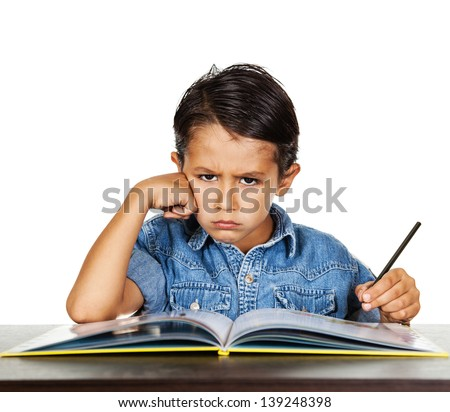 Angry frustrated little boy doing his homework,.