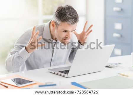 Angry frustrated office worker having problems with his laptop and connection, computer problems and troubleshooting concept