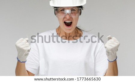 angry girl architect in a construction helmet on a light background