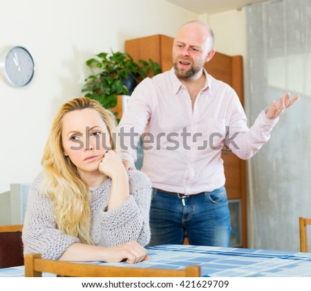 Angry guy and sad woman during quarrel in living room