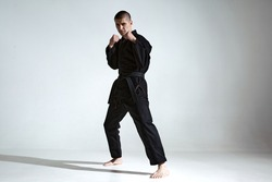 Angry guy trainer in black kimono fighter posing in karate stance on studio background with copy space