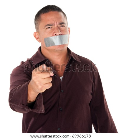 Angry Hispanic man with duct tape over his mouth and pointing finger on white background - stock photo