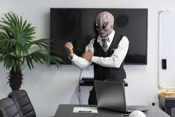 Angry humanoid Alien in a white shirt and business black suit in a conference, meeting room or home office shakes his fist out. CEO Monster gesturing fist in threatening gesture, aggression