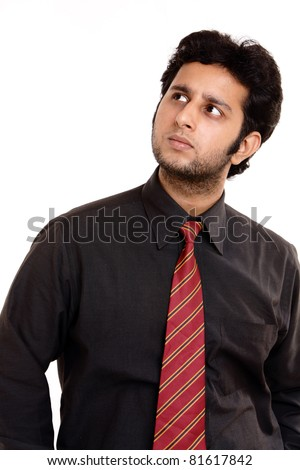 Angry Indian young businessman starring at side.