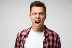 Angry, irate man with grumpy grimace on his face,with mouth opened in shout, ready to argue and swear, wants to gain respect, show strength, isolated over white background