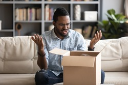 Angry irritated African American man in glasses dissatisfied by received parcel, unhappy customer unpacking cardboard box, wrong or broken fragile online store order, bad delivery service concept