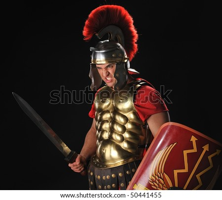 Angry legionary soldier with a gladius and shields - stock photo