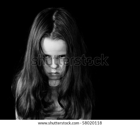 Angry little girl over the black background