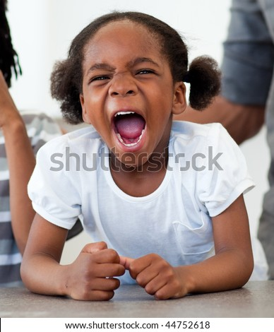 Angry little girl shouting in the kitchen