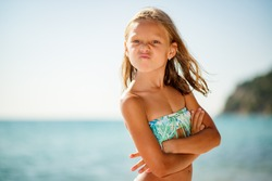 Angry little girl standing on the beach with crossed arms and frowning.