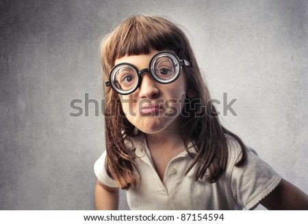 Angry little girl with thick eyeglasses