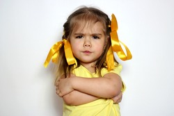 Angry little girl with yellow bows and yellow T-shirt over white background, sign and gesture concept