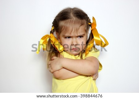 Angry little girl with yellow bows and yellow T-shirt over white background, sign and gesture concept #398844676