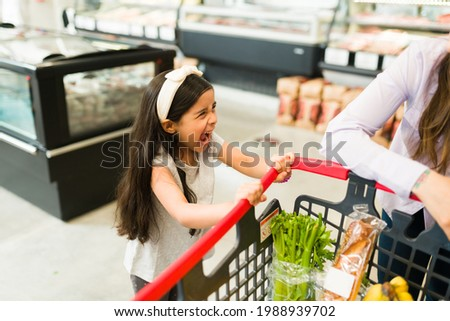 Angry little kid screaming and throwing a tantrum while grocery shopping with her mom at the supermarket because she won't buy her candy