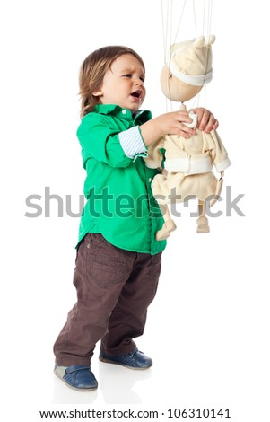 Angry little kid, 2 years old boy, wearing shirt and jeans strangling an wooden puppet,. High resolution image isolated on white background with copy space. Studio shot.