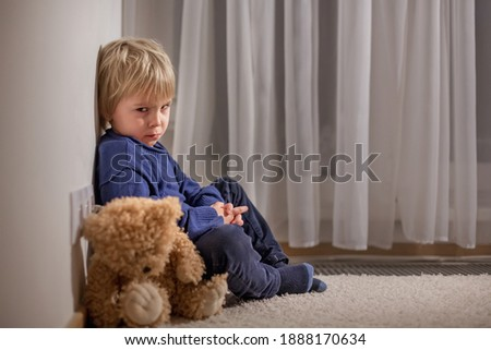 Angry little toddler child, blond boy, sitting in corner with teddy bear, punished for mischief Stock photo ©