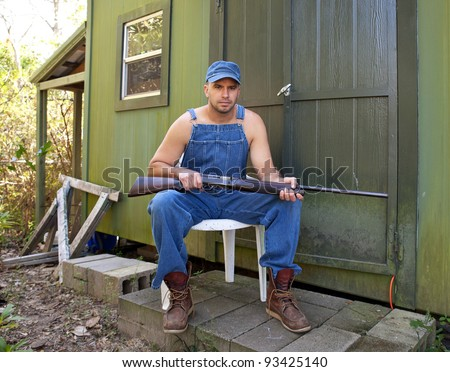 Angry looking young man in old overalls, seated and holding a shotgun outside a cabin or hunting camp.