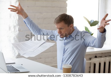 Angry mad businessman sitting at workplace throwing documents paper feels nervous unable control emotions and handle the stress at work. Bad day, problems in business huge debts and bankruptcy concept