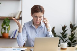 Angry mad businesswoman talking on phone looking at laptop, annoyed stressed office worker arguing with client by mobile solving online computer business problem with technical customer support