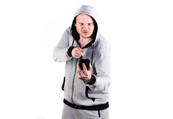 Angry man arguing with his smart phone and pointing right into a screen, screaming and fizzles because of storm of emotions. Dressed in grey hooded sport suit. Isolated. white background.