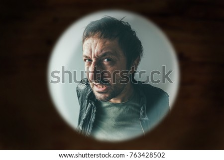 Angry man at the door viewed through spy hole, debt collector or criminal knocking at the door