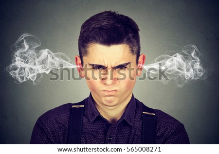 Angry man, blowing steam coming out of ears, about to have nervous breakdown isolated on gray background. Negative human emotions facial expression