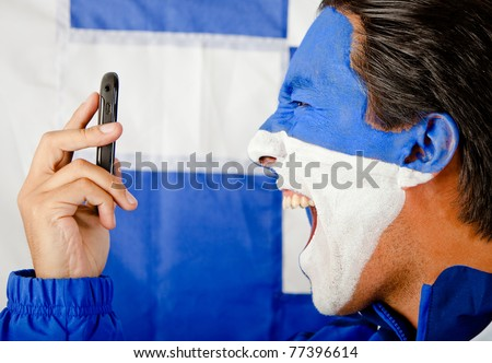 Angry man calling Greece and yelling with the flag painted on his face