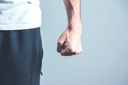 angry man fist on the gray wall background
