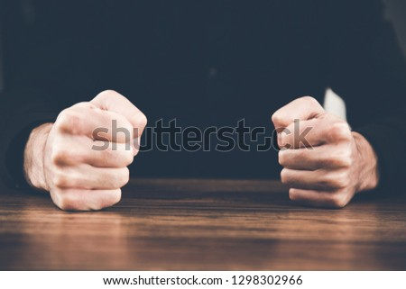 angry man fists on table