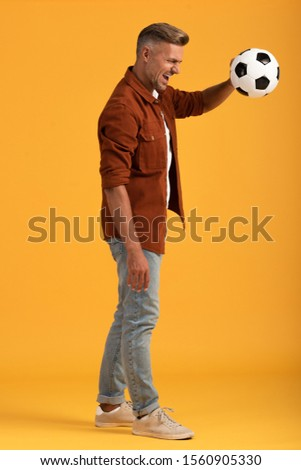 angry man holding football standing standing on orange  #1560905330