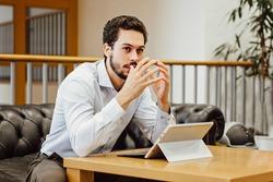 Angry man in despair working on laptop