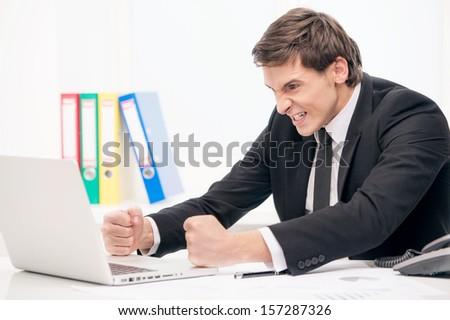 Angry man looking at laptop