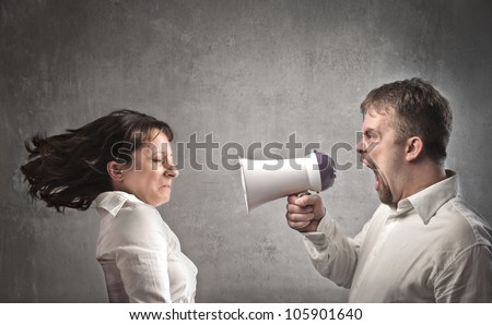 Angry man shouting against his girlfriend with the help of a megaphone