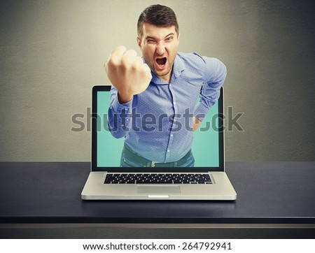 angry man with big fist got out of the laptop and screaming against dark background