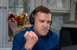 Angry man with headphones clenched his fist, looking at laptop screen, writes offensive comments to haters, spreads fake rumors, feeds trolls online. Concept hate, trolling, anger on Internet forum