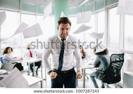Angry manager in white shirt standing angrily at his desk. Throwing papers. #1007287243
