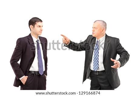 Angry mature man in a suit pointing with a finger towards a young man in a suit isolated on white background