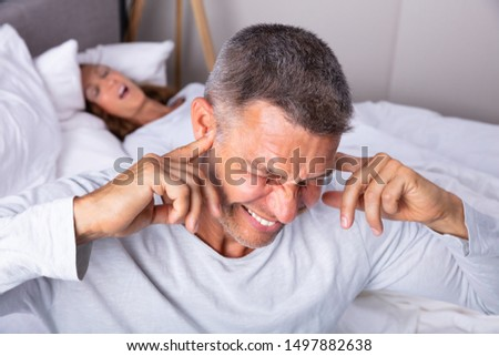 Angry Mature Man Plugging Ear With Finger While Sitting Near Snoring Wife In Bed