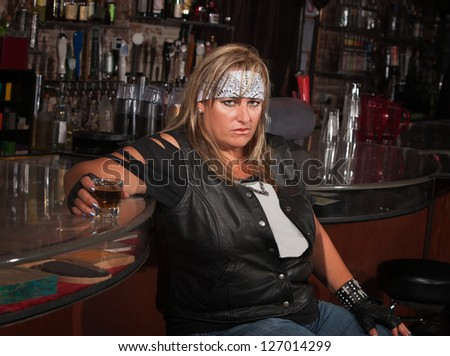 Angry mature woman with alcohol leaning back in a tavern