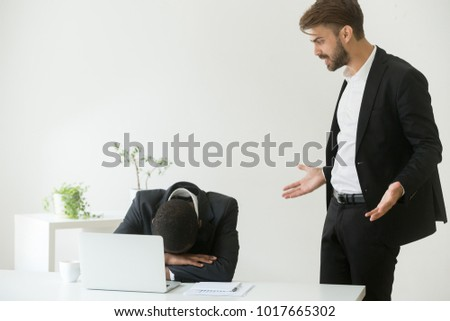 Angry mean caucasian boss shouting scolding frustrated incompetent african american employee for bad work or business failure, white executive reprimands sad black subordinate, racial discrimination