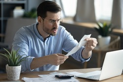 Angry millennial Caucasian guy sit at desk managing financial paperwork frustrated by bill amount. Unhappy young man feel distressed confused paying online, calculating expenses expenditures at home.