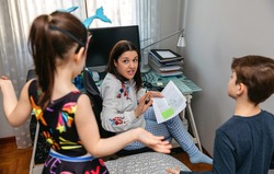 Angry mother scolding her children who interrupt her while telecommuting at home. Conciliation family work concept